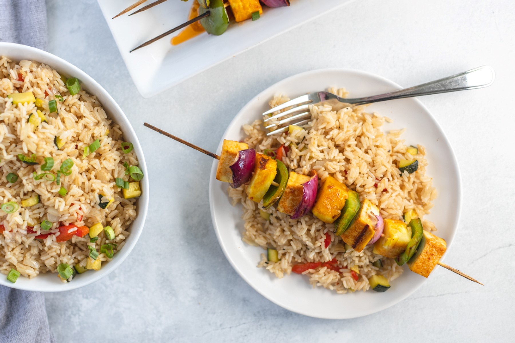 Plate of fried rice with a cooked Hawaiian grilled tofu skewer on top with a bowl of fried rice and fork on the plate.