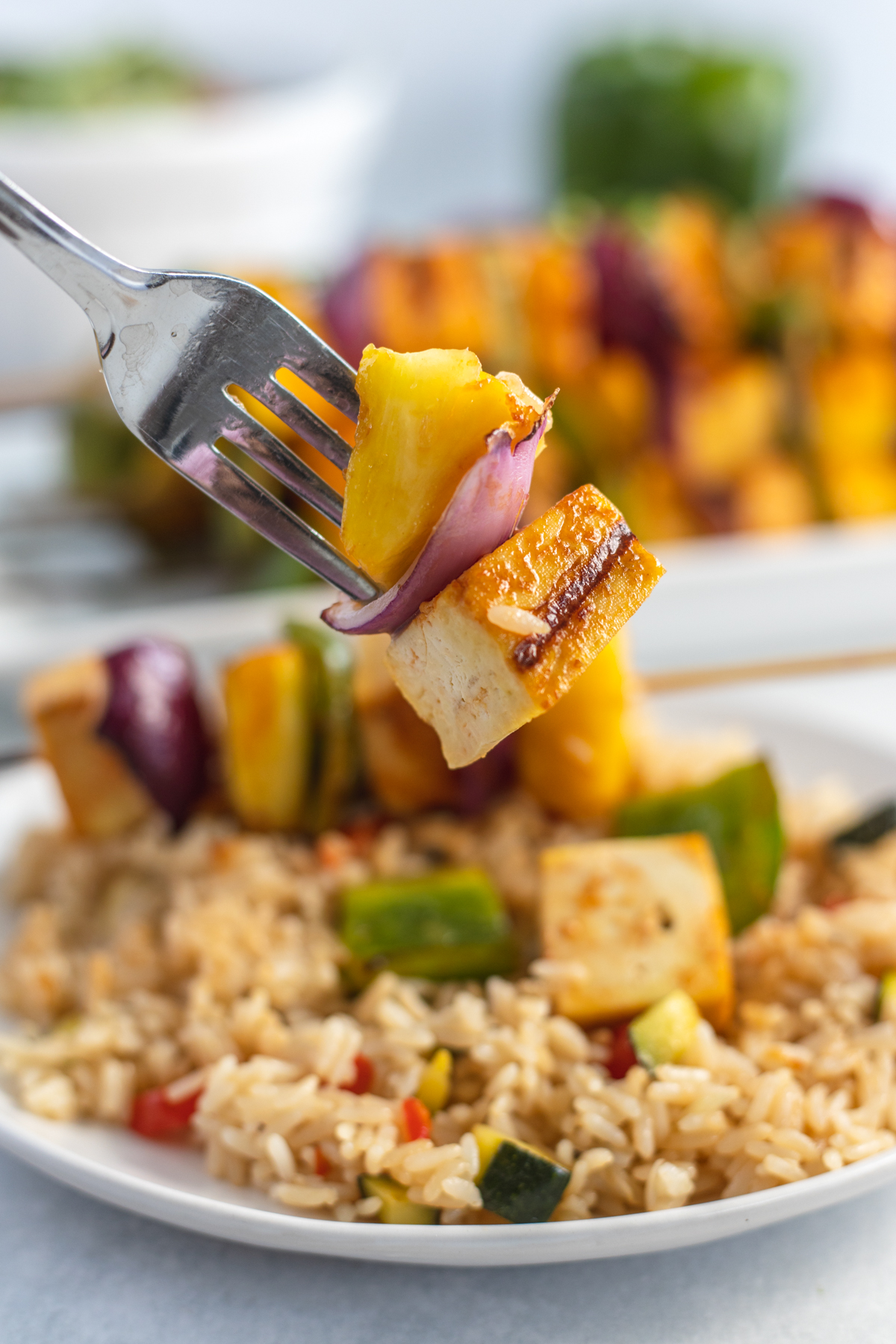 Fork with a piece of grilled tofu, pineapple, and red onion.