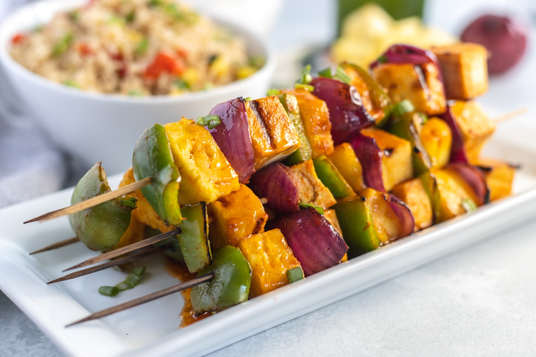 Stack of cooked Hawaiian grilled tofu skewers on a white platter.