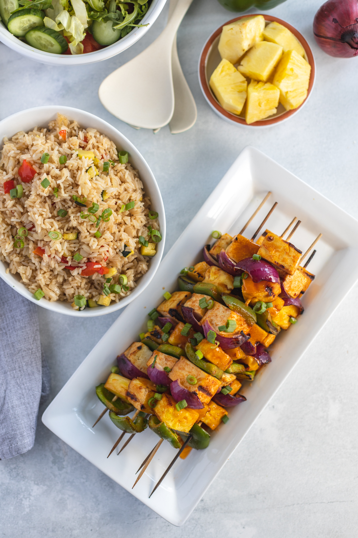 Platter of cooked Hawaiian grilled tofu skewers with a bowl of fried rice and pineapple chunks