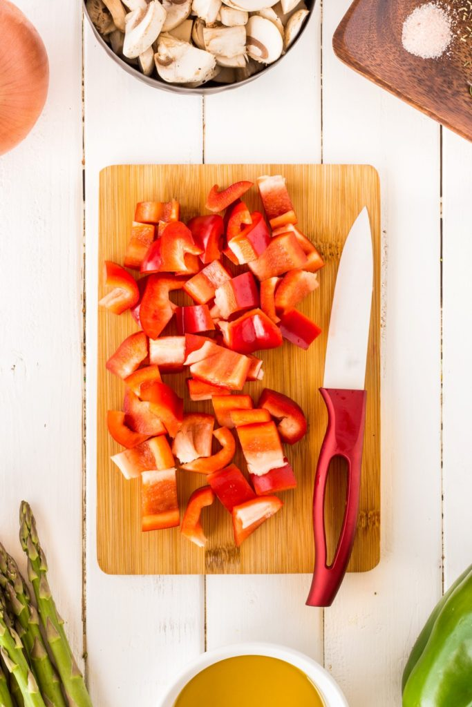 Chopped red pepper with a knife on a wooden cutting board