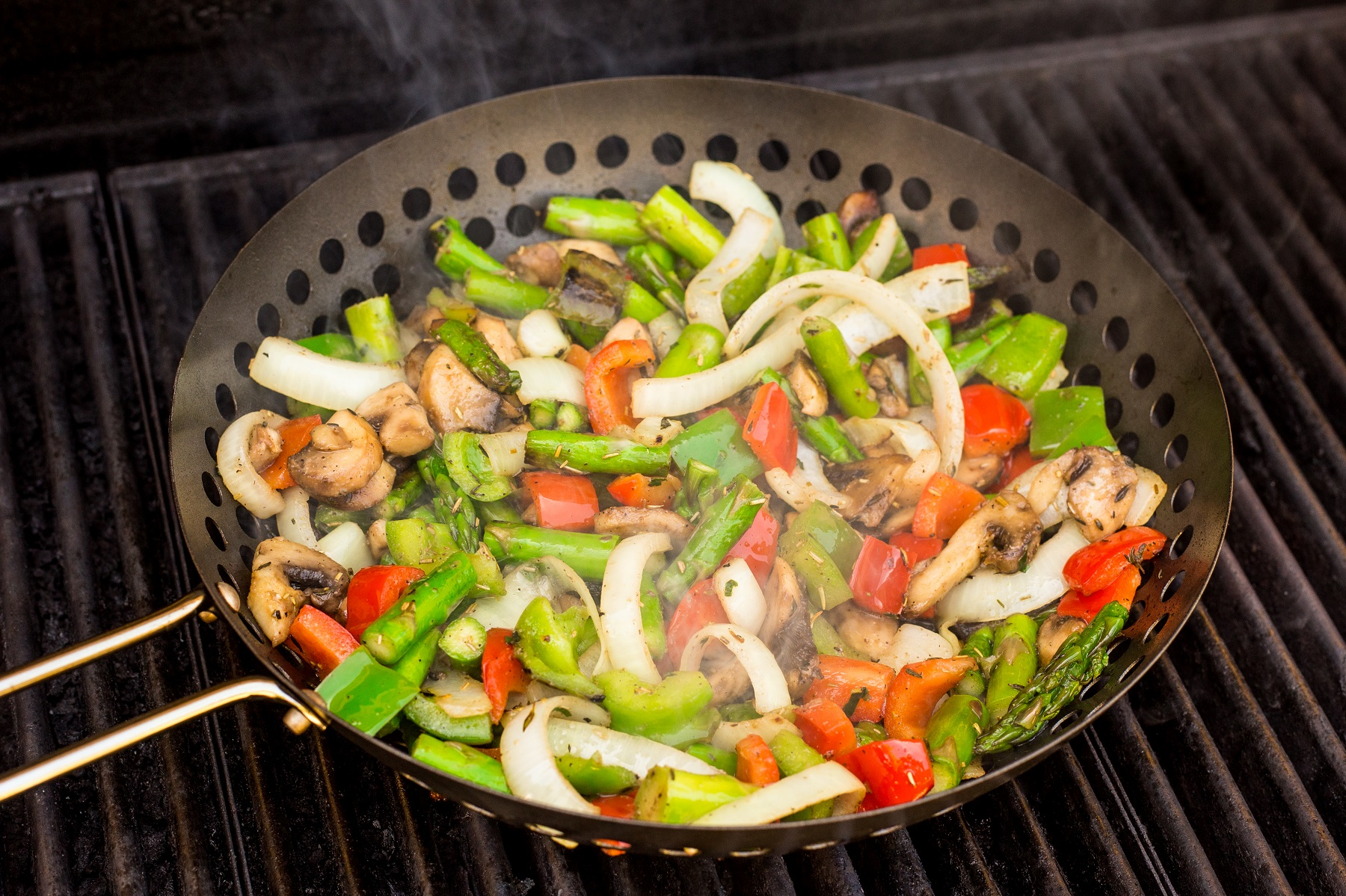 BBQ wok full of diced vegetables on a hot BBQ grill