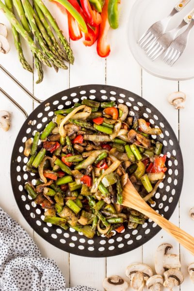 BBQ wok vegetables on a wooden board with a wooden spoon in the wok