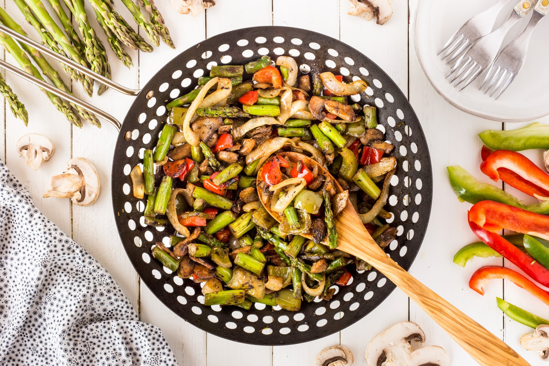 Cooked BBQ wok vegetables on a wooden board with a wooden spoon scooping out a spoonful