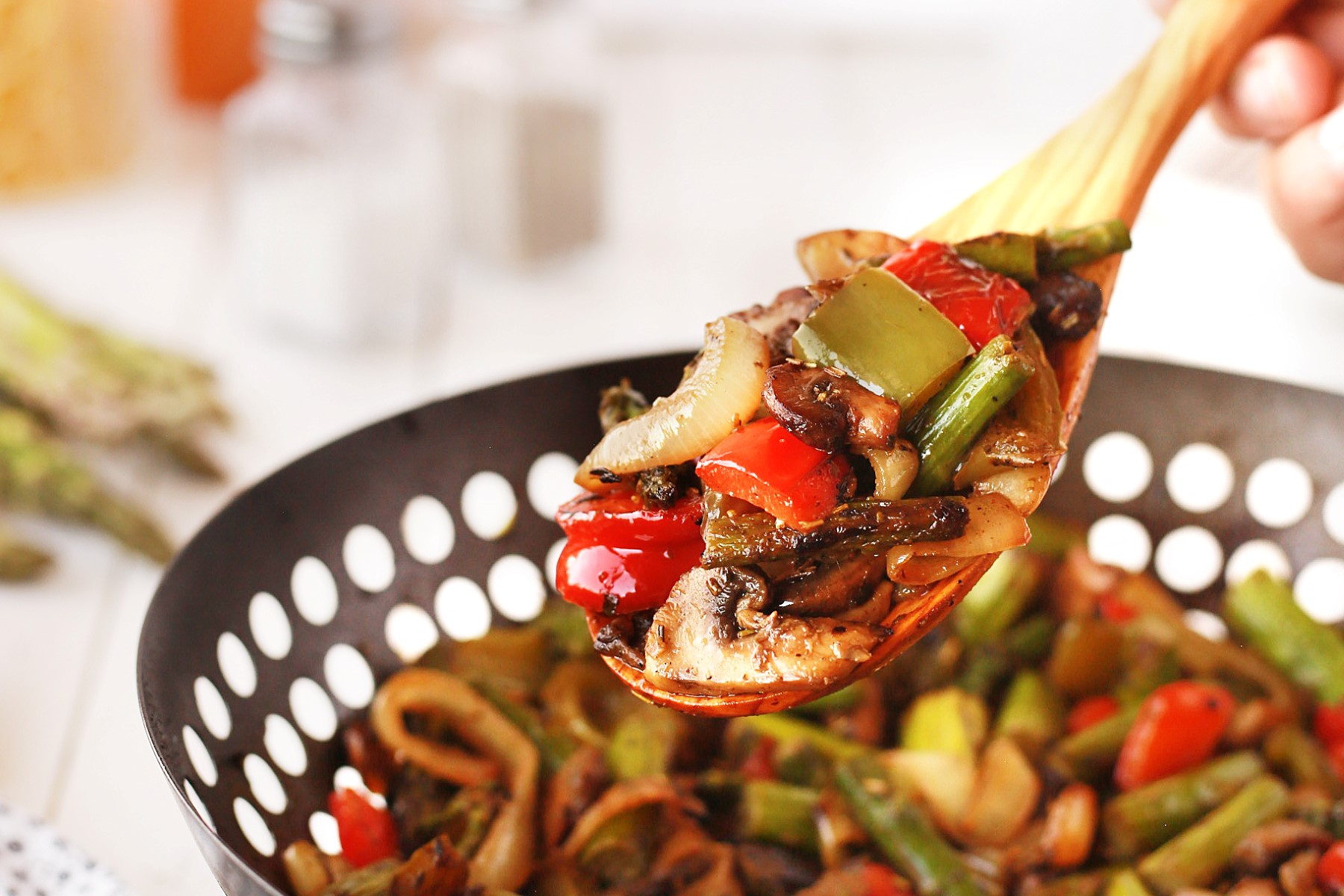 Wooden spoonful of cooked vegetables with the BBQ wok in the background.