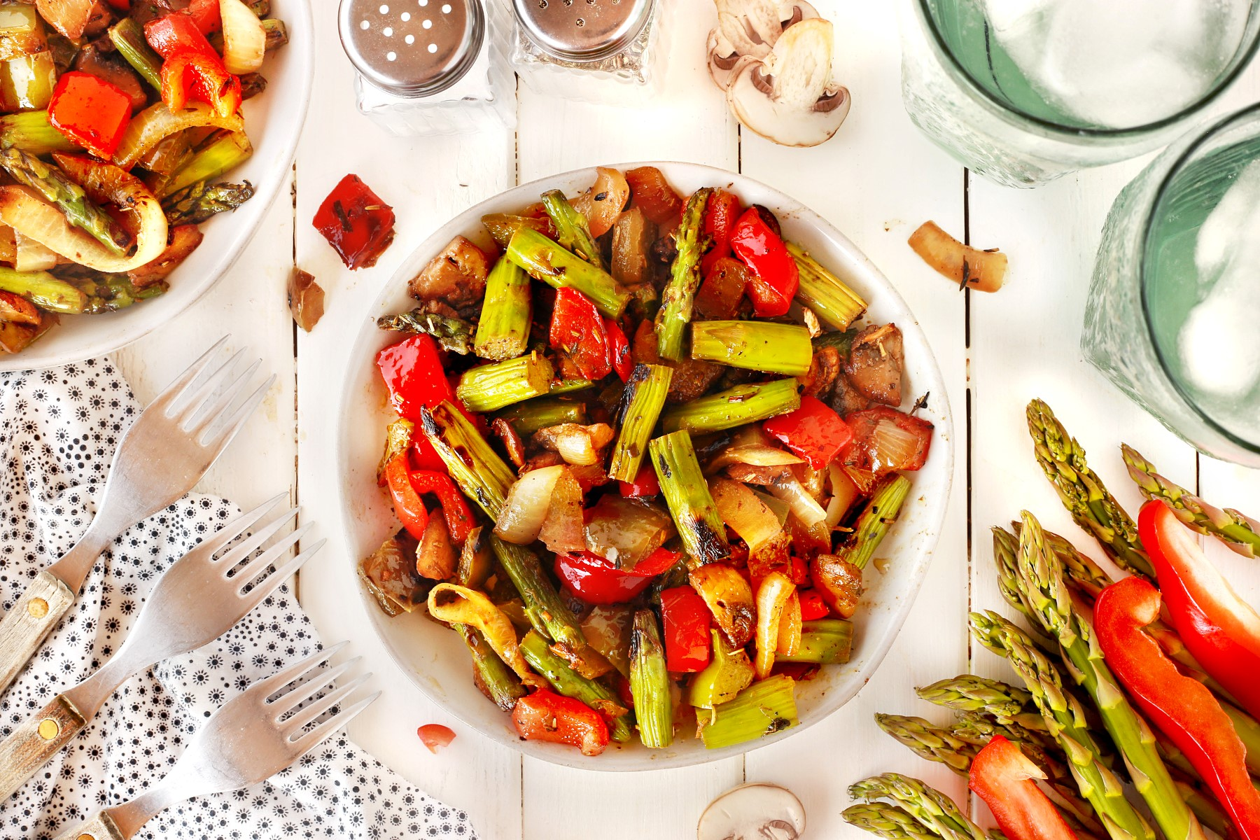 BBQ wok vegetables in a white serving bowl on a table with forks and fresh vegetables around.
