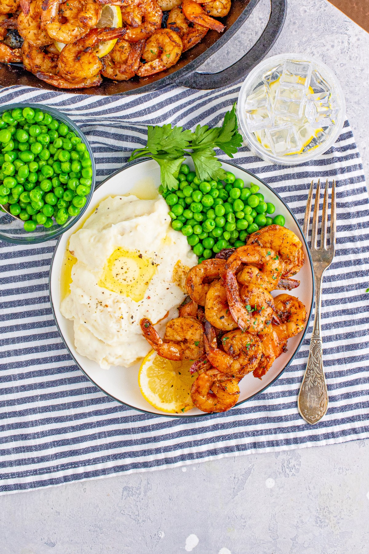 Blackened shrimp on a white plate with peas and mashed potatoes, with a small bowl of peas and a cast iron skillet of blackened shrimp beside the plate.