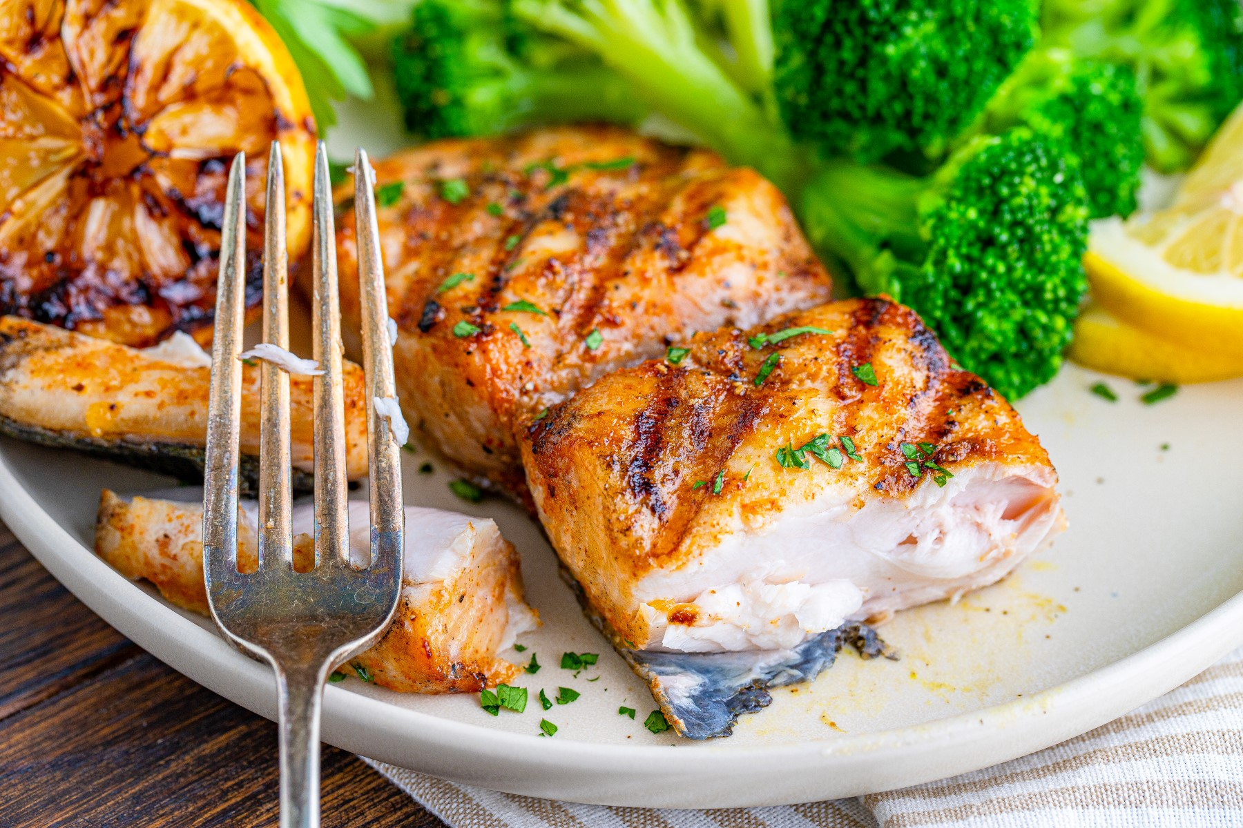 Grilled mahi mahi cut showing the center of the fillet on a white plate with a fork and broccoli.