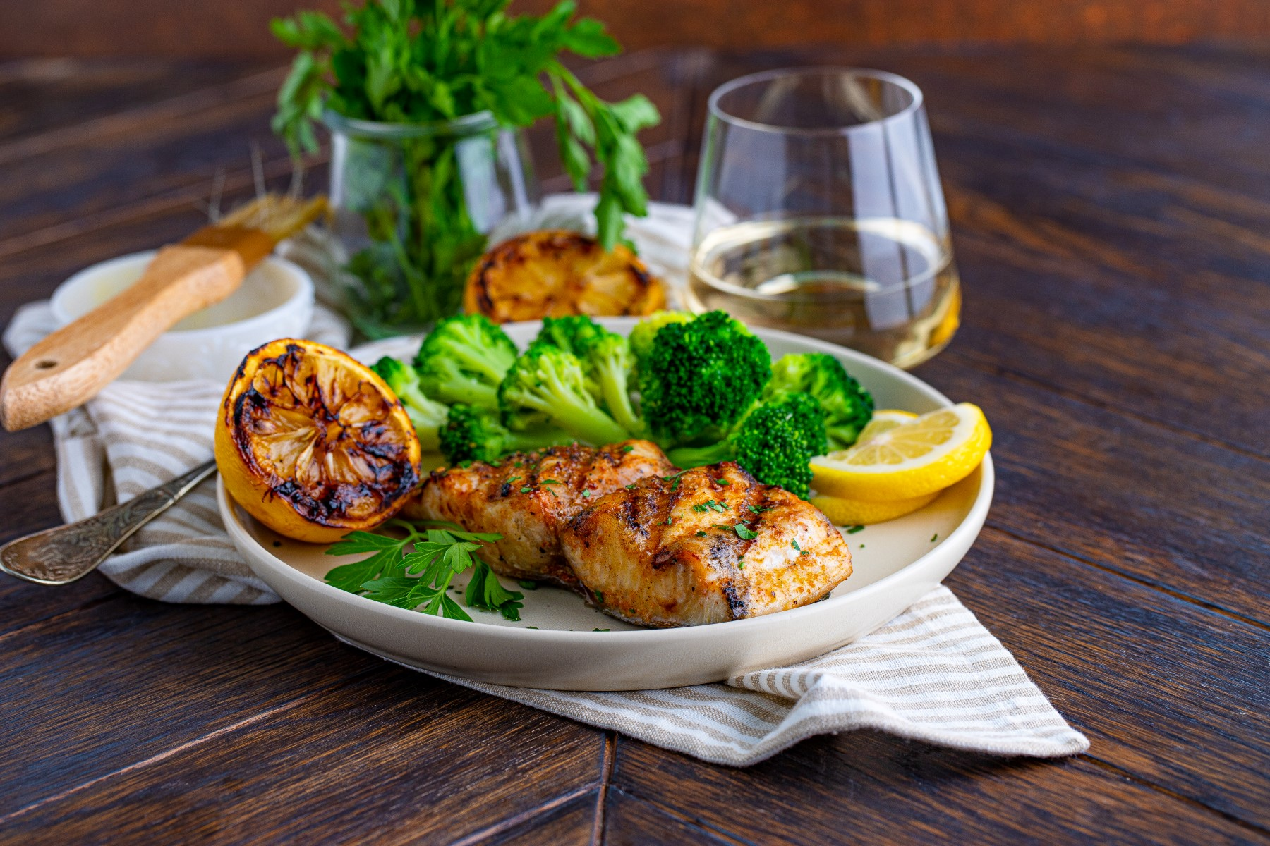 Grilled Mahi Mahi on a white plate with a grilled lemon halve and broccoli, with a glass of white wine.