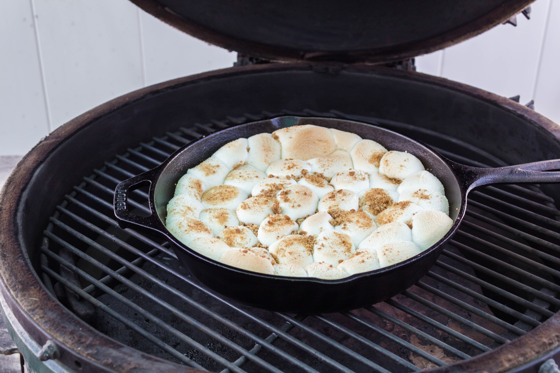 Cast iron skillet of s'mores on a BBQ grill with the marshmallows toasted on top.