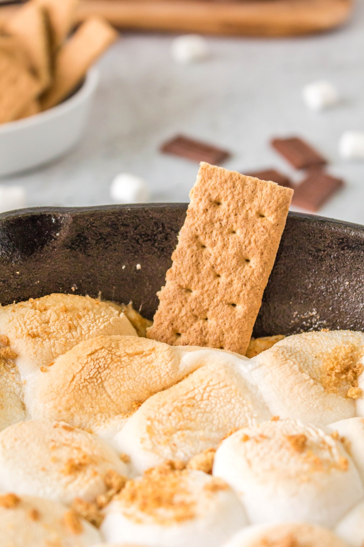 BBQ s'mores dip in a cast iron pan with a graham cracker stuck in the toasted marshmallows.