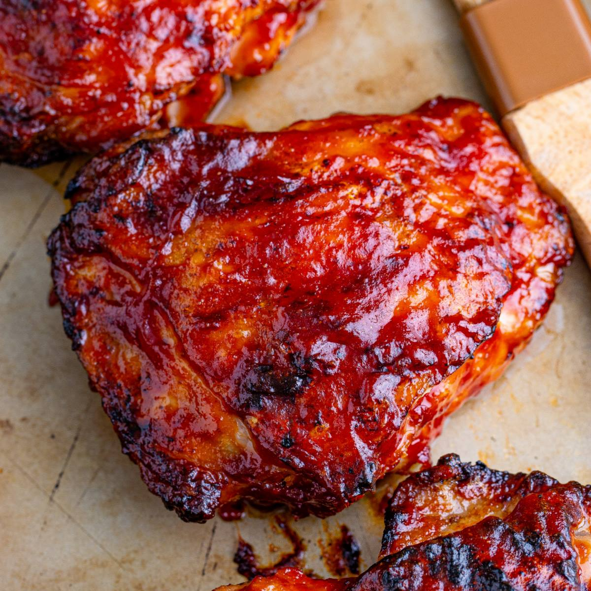 Grilled BBQ chicken thighs covered with BBQ sauce on a cutting board