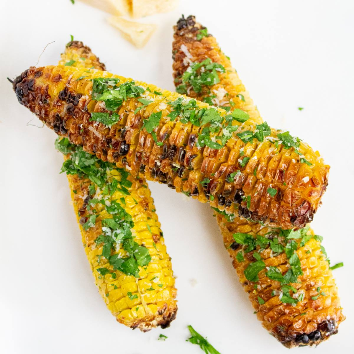 3 cobs or grilled corn and the cob on a white plate with grated parmesan and chopped parsley