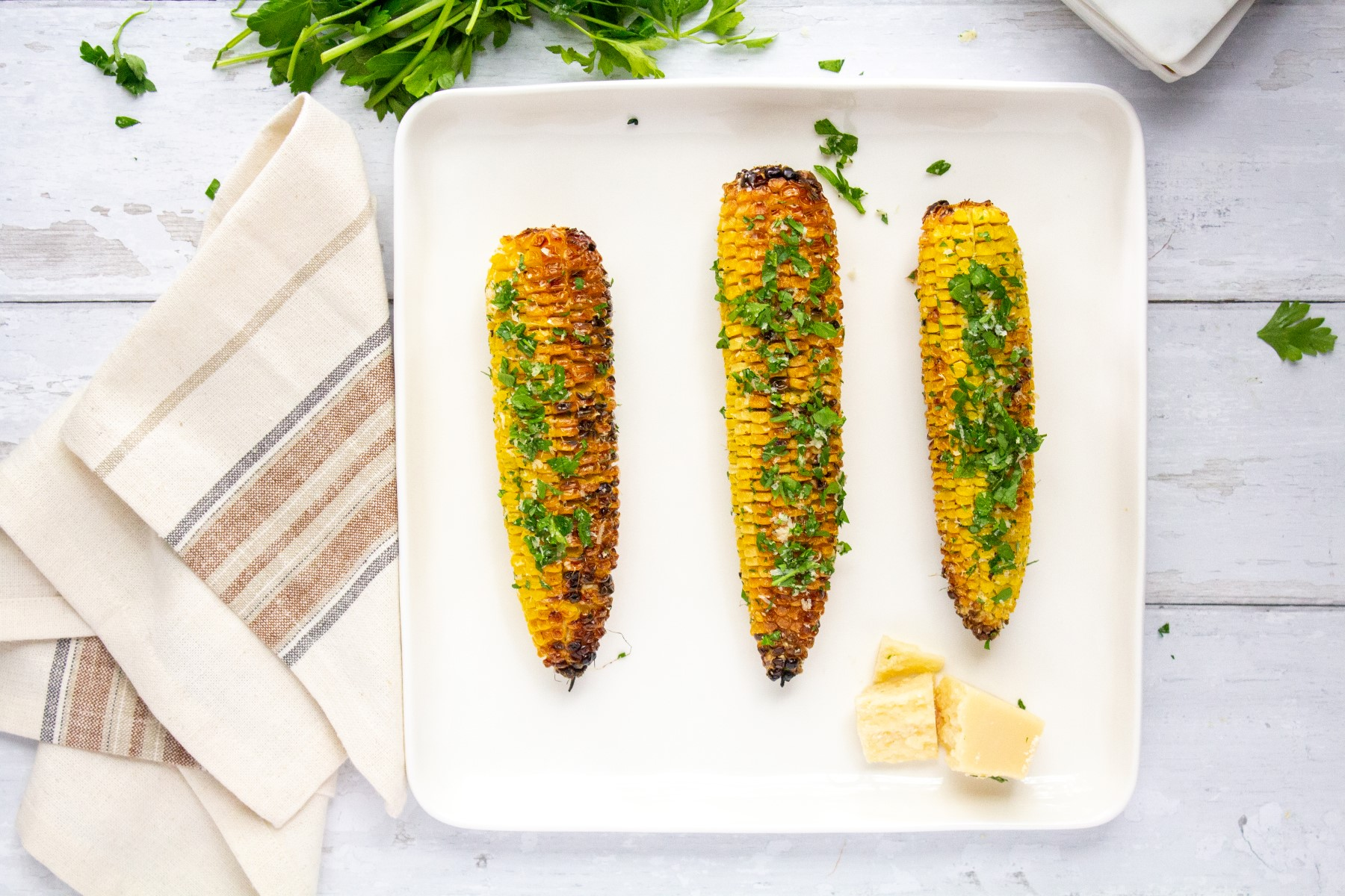 3 cobs of grill corn on the cob on a white platter, sitting on a white wooden table.