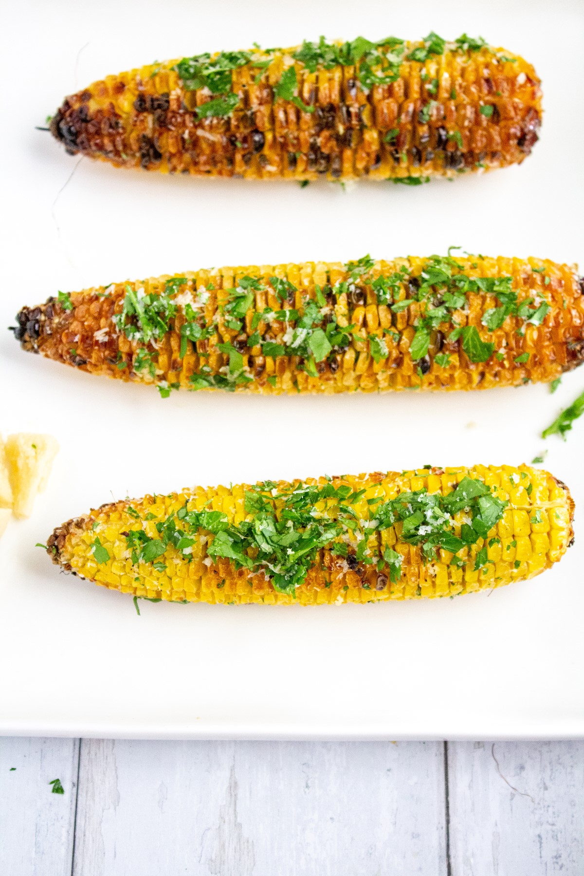 3 grilled cobs of corn covered with grated parmesan cheese, chopped parsley and minced garlic on a white plate.