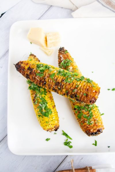 3 cobs of grilled corn stacked on a white plate plater
