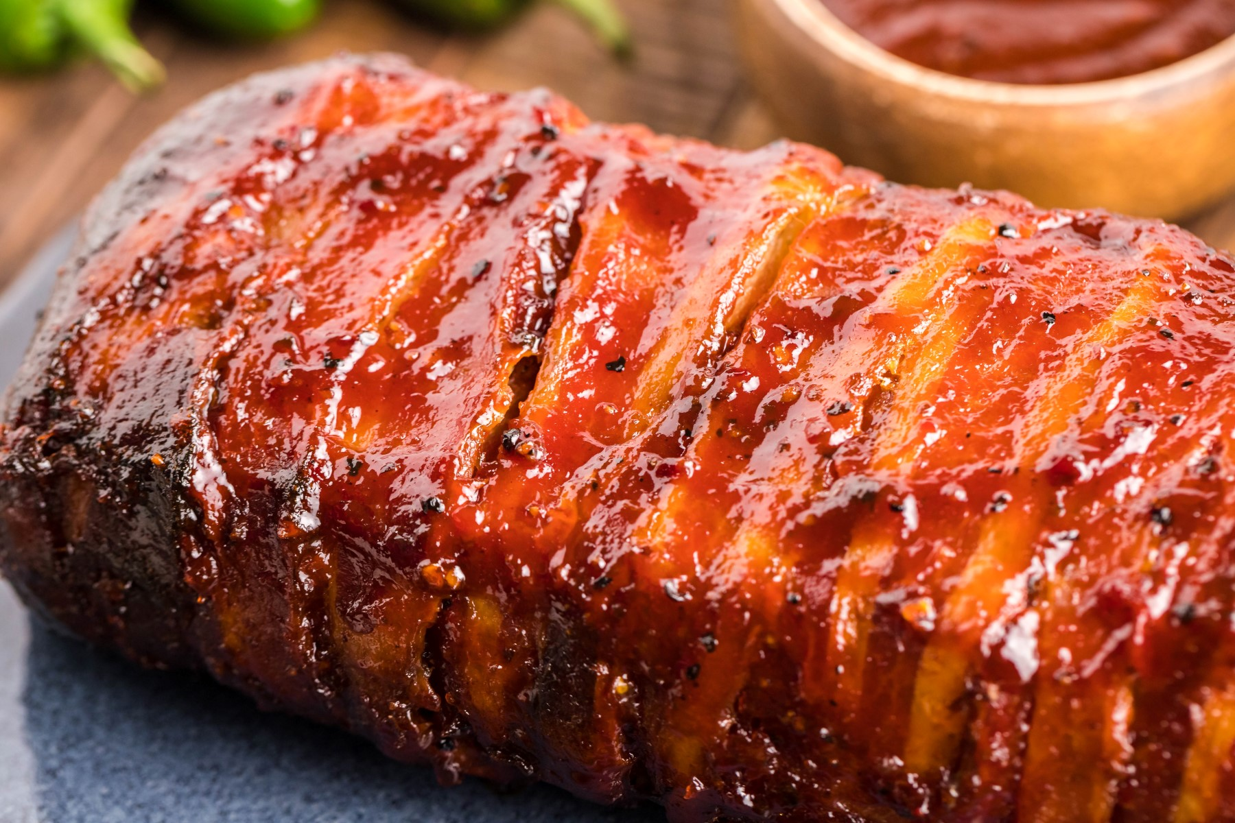 Fully smoked Bacon wrapped sausage roll covered with BBQ sauce on a cutting board.