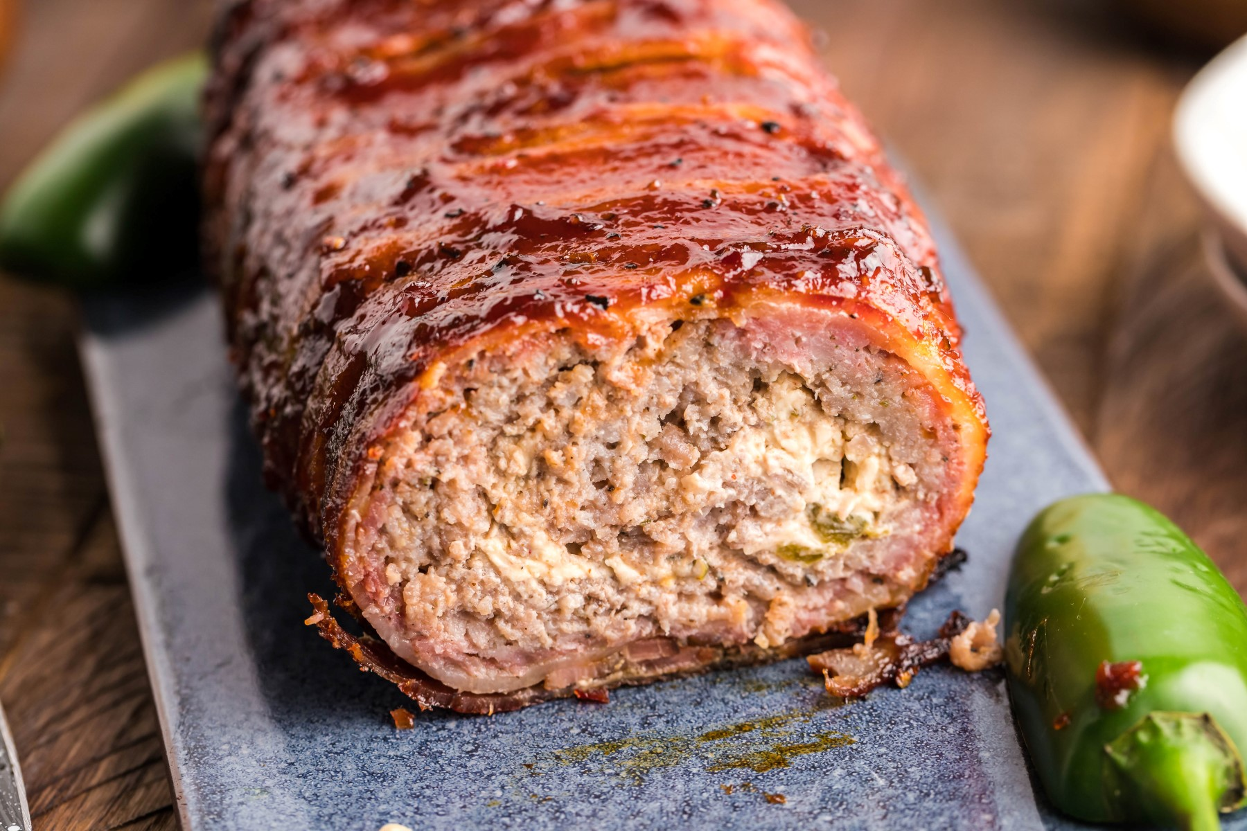 Bacon wrapped sausage roll with the end cut off sitting on a cutting board with a whole jalapeno on the board