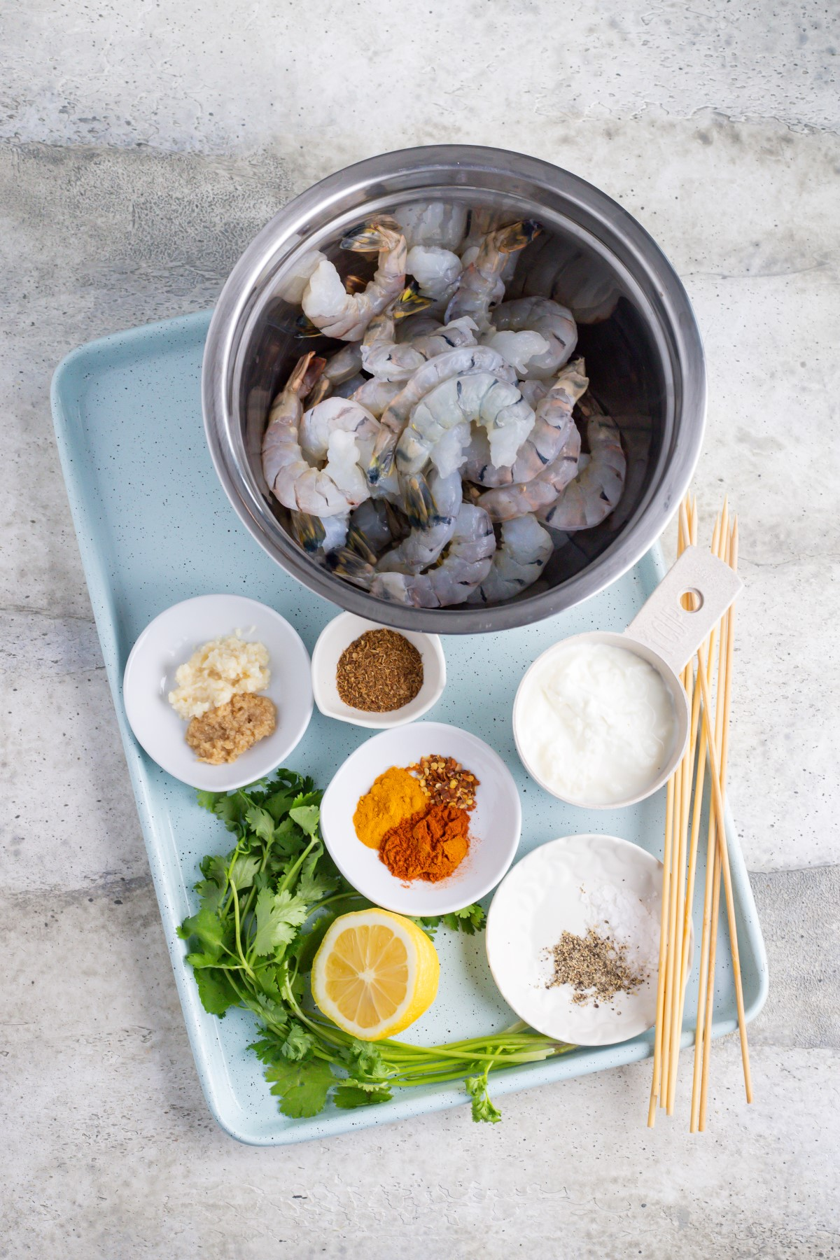 All the ingredients for the tandoori shrimp skewers in small bowls on a light blue tray, with bamboo skewers beside the bowls.