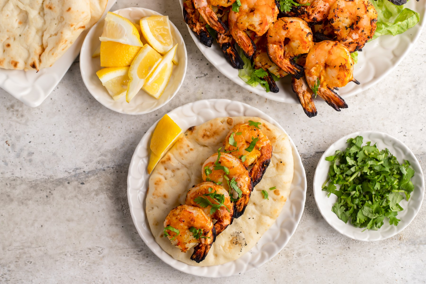 Grilled Tandoori Shrimp on naan bread with chopped parsley and lemon wedges