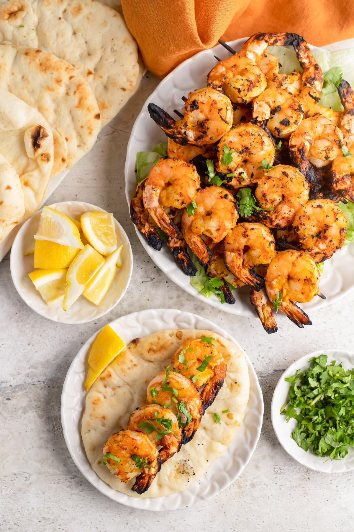 Grilled Tandoori Shrimp in a single layer on naan bread wit lemon wedges and a large plate of cooked shrimp on skewers