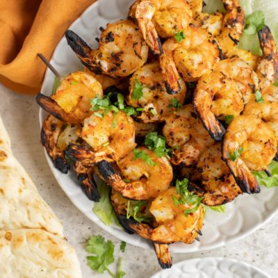 Grilled Tandoori shrimp skewers ona white plate with naan bread