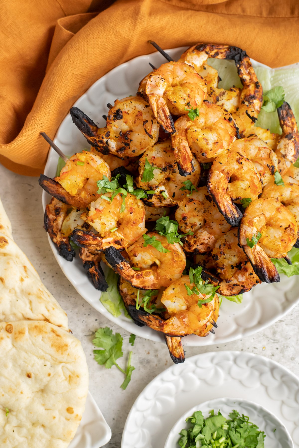 Grilled Tandoori Shrimp skewers on a white plate garnished with chopped parsley.