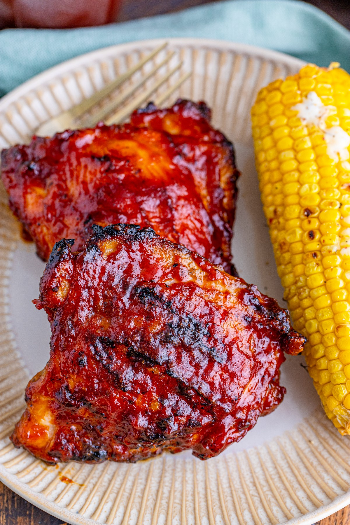 BBQ Chicken Thighs on a white plate with a grilled cob of corn beside the chicken.