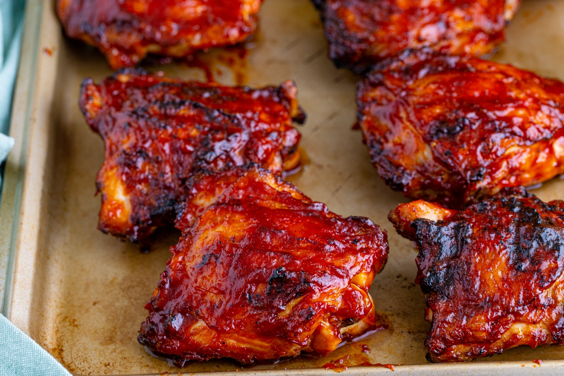 Grilled BBQ bone in chicken thighs on a baking sheet covered with BBQ sauce.