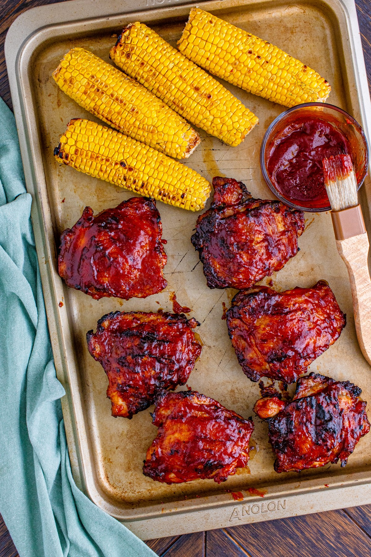 Grilled BBQ chicken thighs covered in BBQ sauce on a baking sheet with grilled cobs of corn and a glass bowl filled with BBQ sauce and a brush