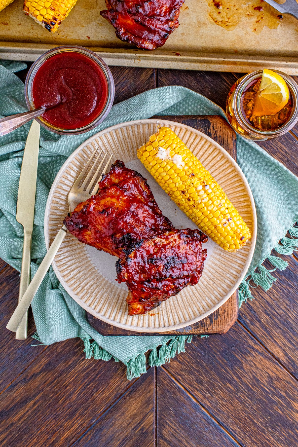 Grilled BBQ chicken covered in BBQ sauce on a cream colored plate with grilled corn on the cob and a knife and fork.