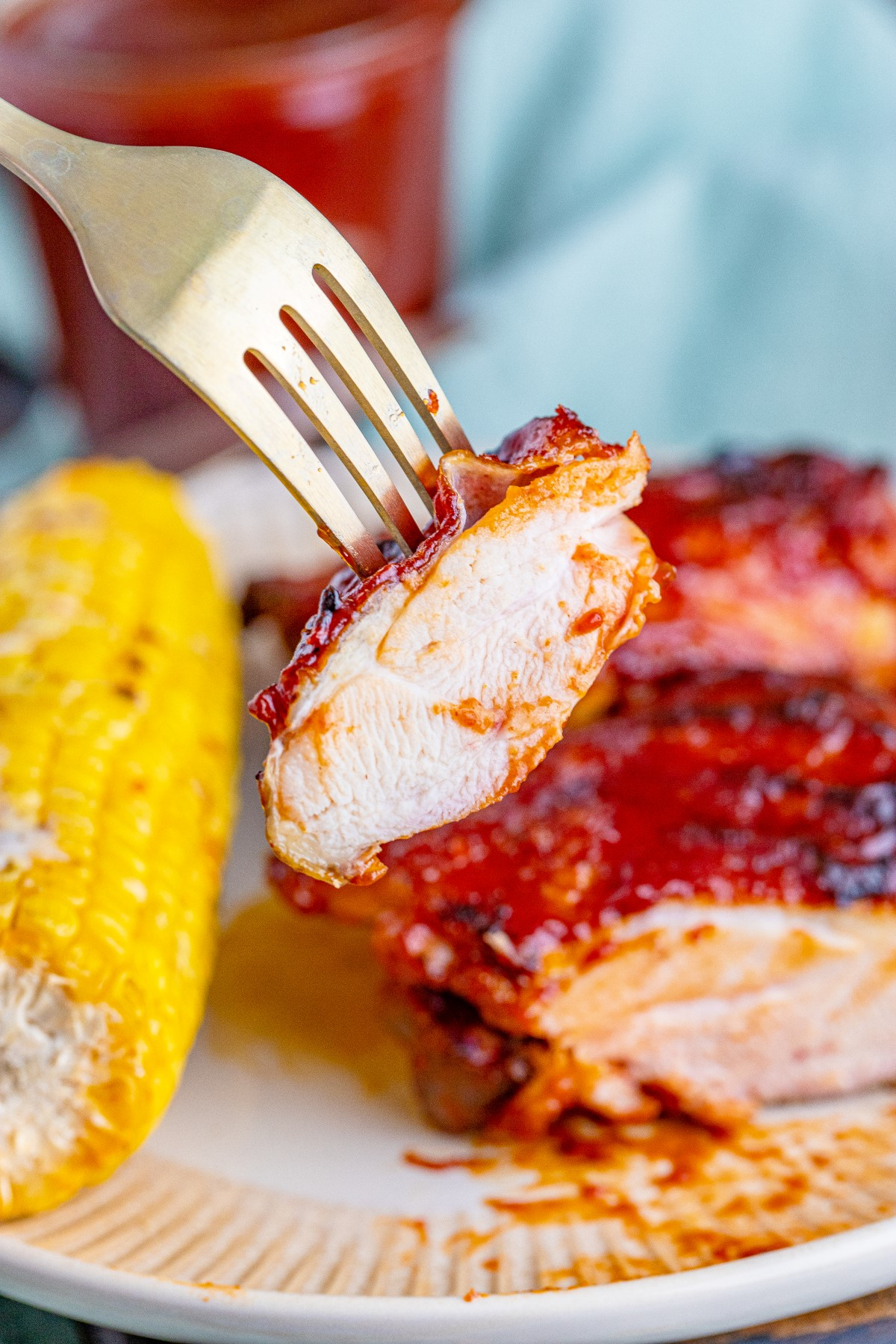 A bite of grilled BBQ chicken thigh on a fork