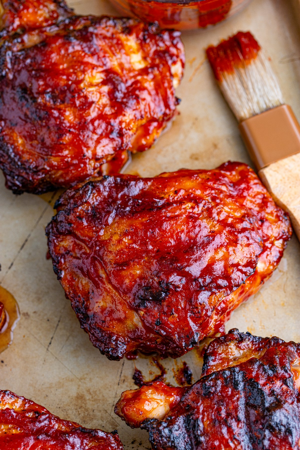 Cooked grilled chicken thighs covered in BBQ sauce.