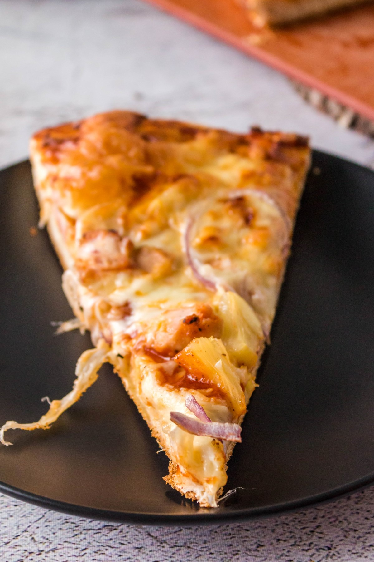 Slice of BBQ chicken pizza on a black plate