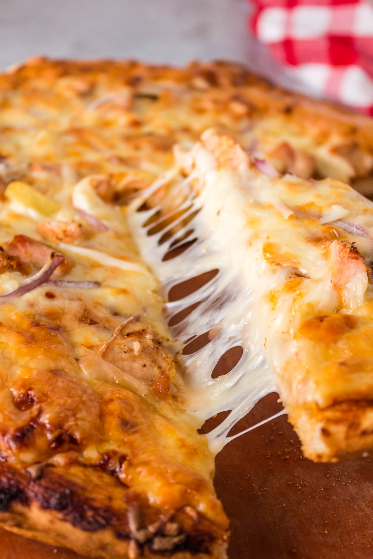 A slice of BBQ chicken pizza being lifted form the platter and the cheese is pulling and stretching