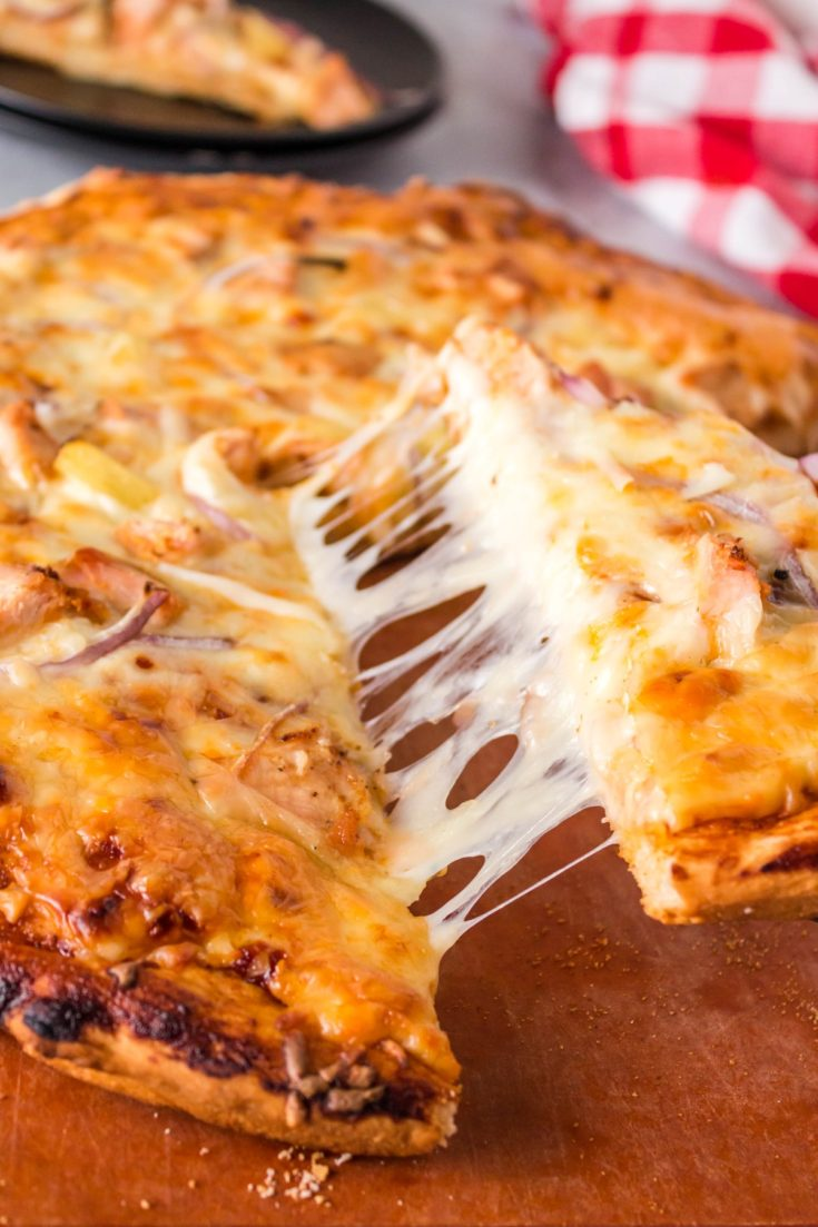 BBQ Chicken Pizza on a wooden board with a slice of pizza being picked up and the cheese pulling and stretching