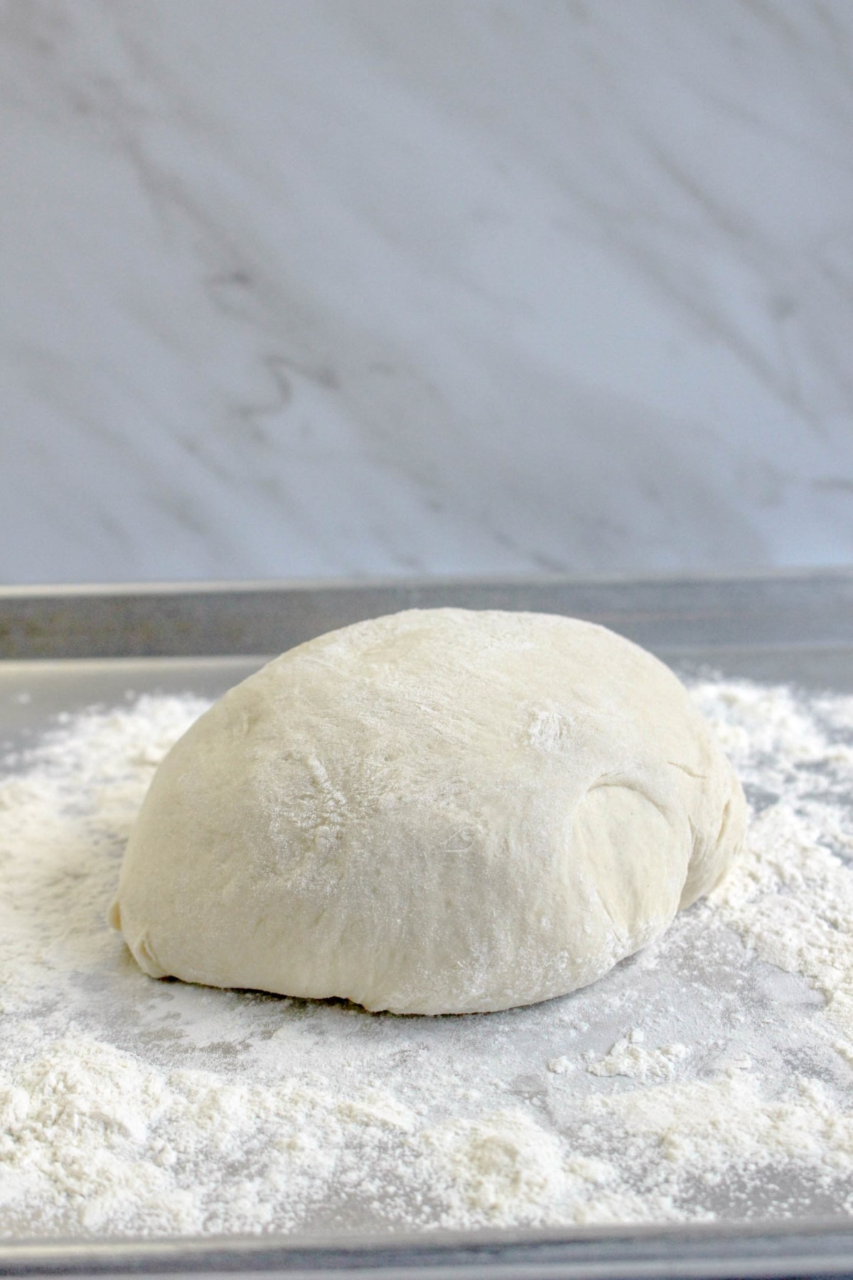 Pizza dough in a ball, resting on a floured surface