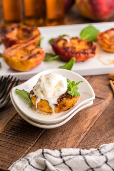 Grilled half peach on a white plate with a scoop of vanilla ice cream on top.