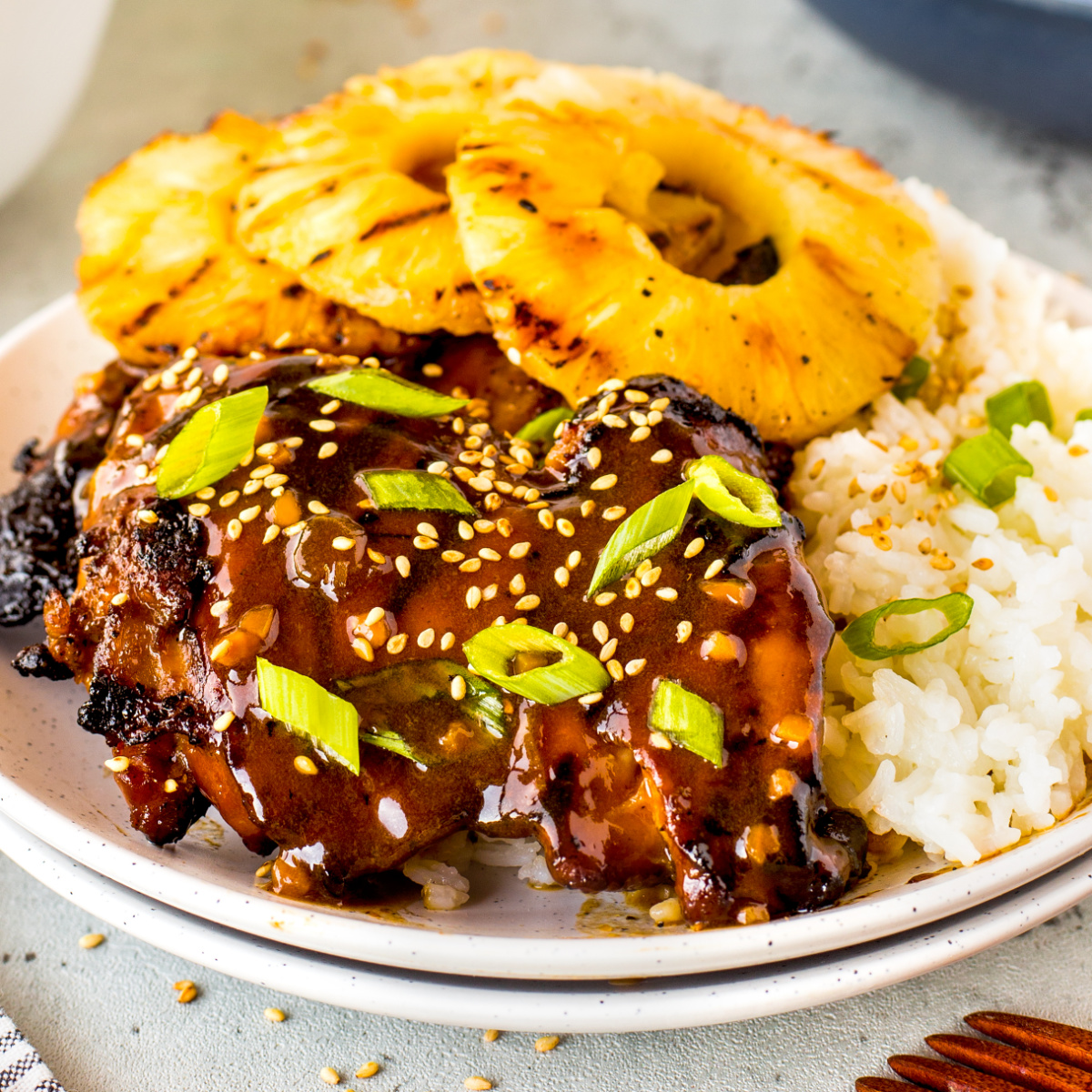 Hawaiian grilled chicken served with grilled pineapple rings and rice on a white plate