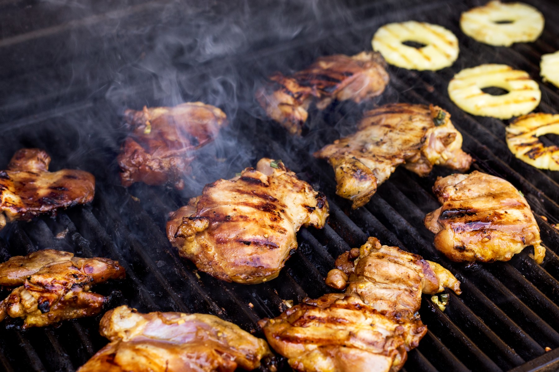 Chicken thighs and pineapple rings grilling on the BBQ.