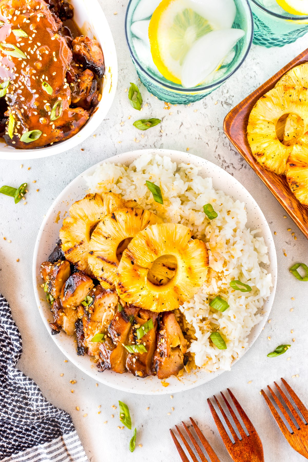 Hawaiian Grilled Chicken on a white plate with rice and pineapple rings with a platter of chicken and plate of grilled pineapple rings beside.