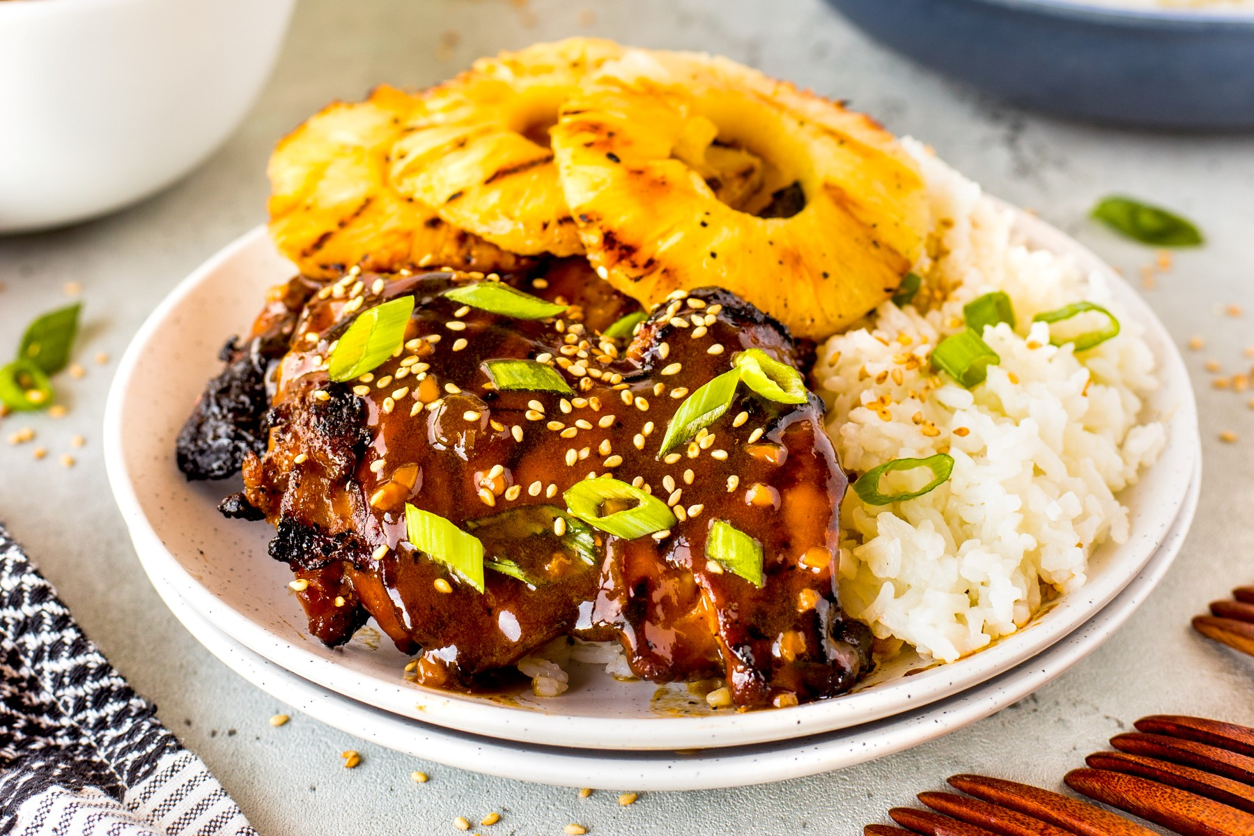 Hawaiian grilled chicken thighs on a white plate served with grilled pineapple rings and rice.