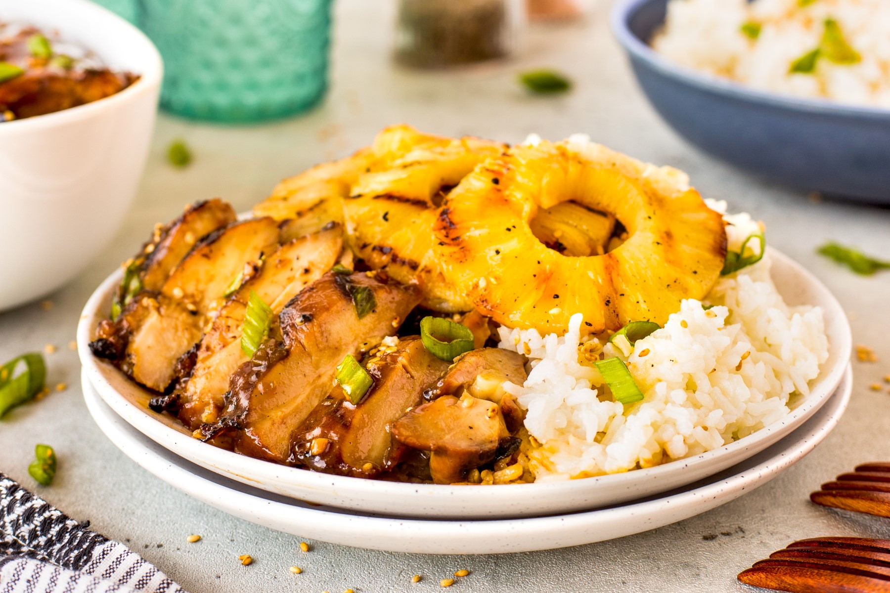 Sliced Hawaiian grilled chicken on a white plate with rice and grilled pineapple rings.