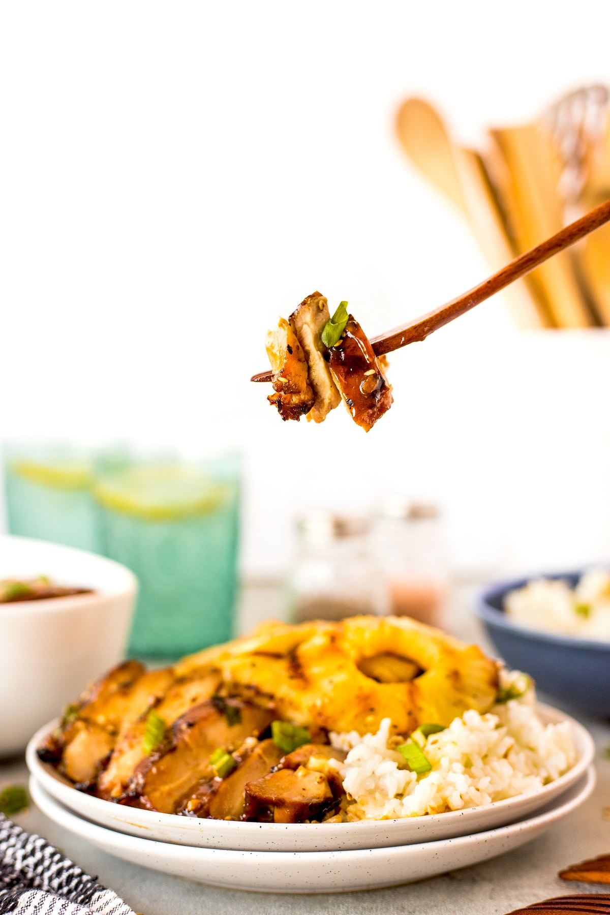 Hawaiian grilled chicken bite on a fork with the sliced grilled chicken, rice and grilled pineapple on the plate below.