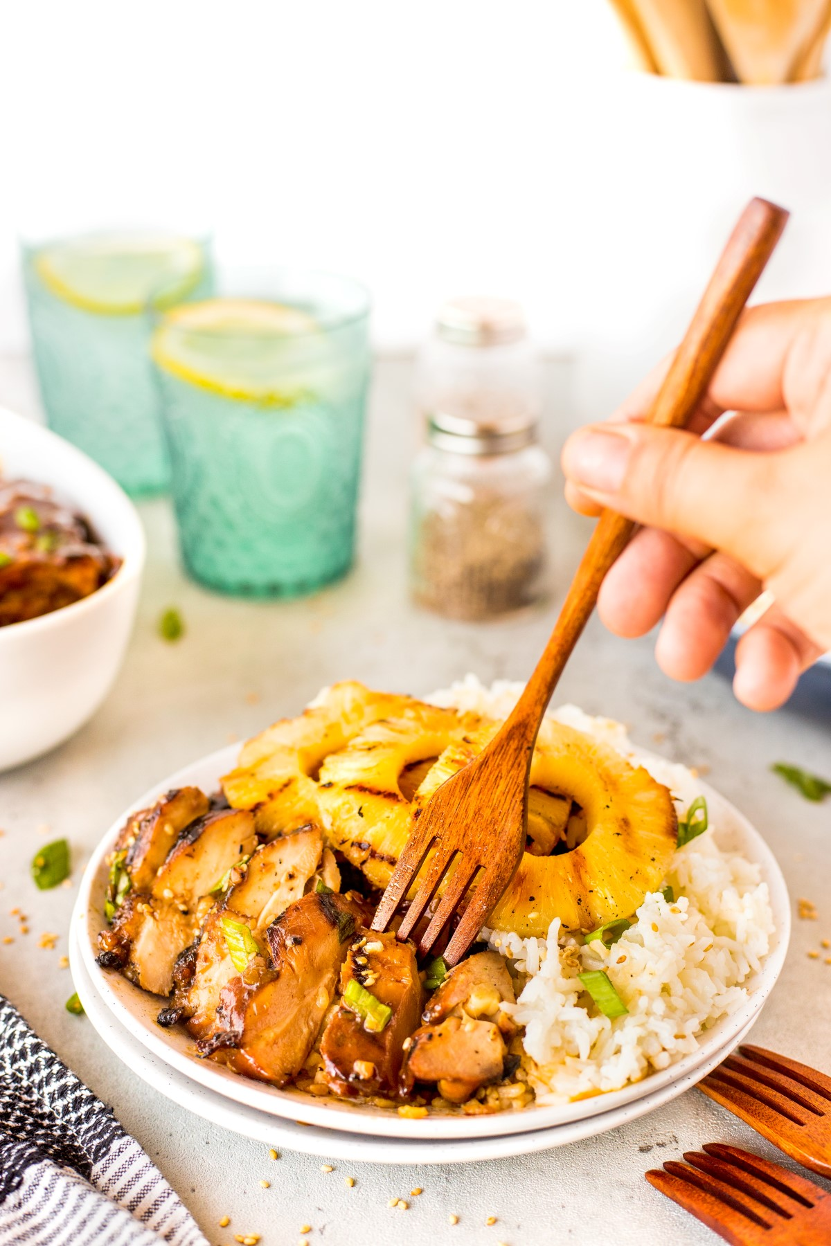 Sliced Hawaiian grilled chicken on a plate with grilled pineapple and rice with a fork on a slice of the chicken.