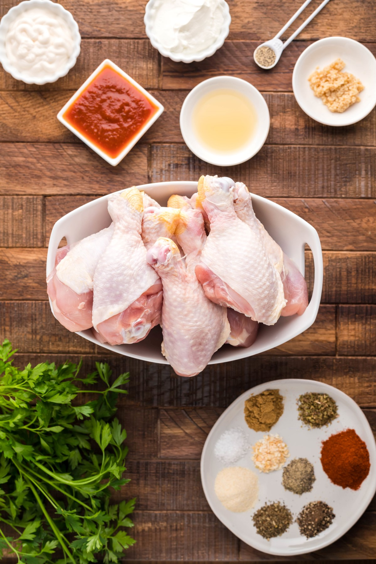 All the ingredients to make dry rub smoked chicken drumsticks on a wooden board, divided into small bowls, plates and spice piles.