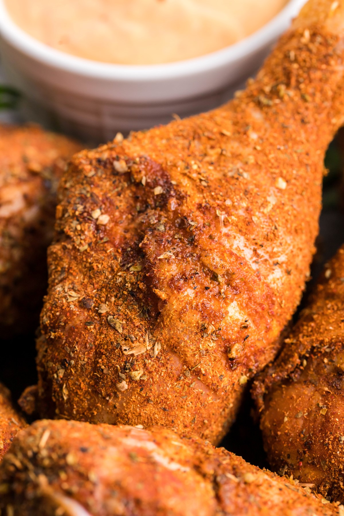 Close up of a smoked chicken drumstick with dry rub