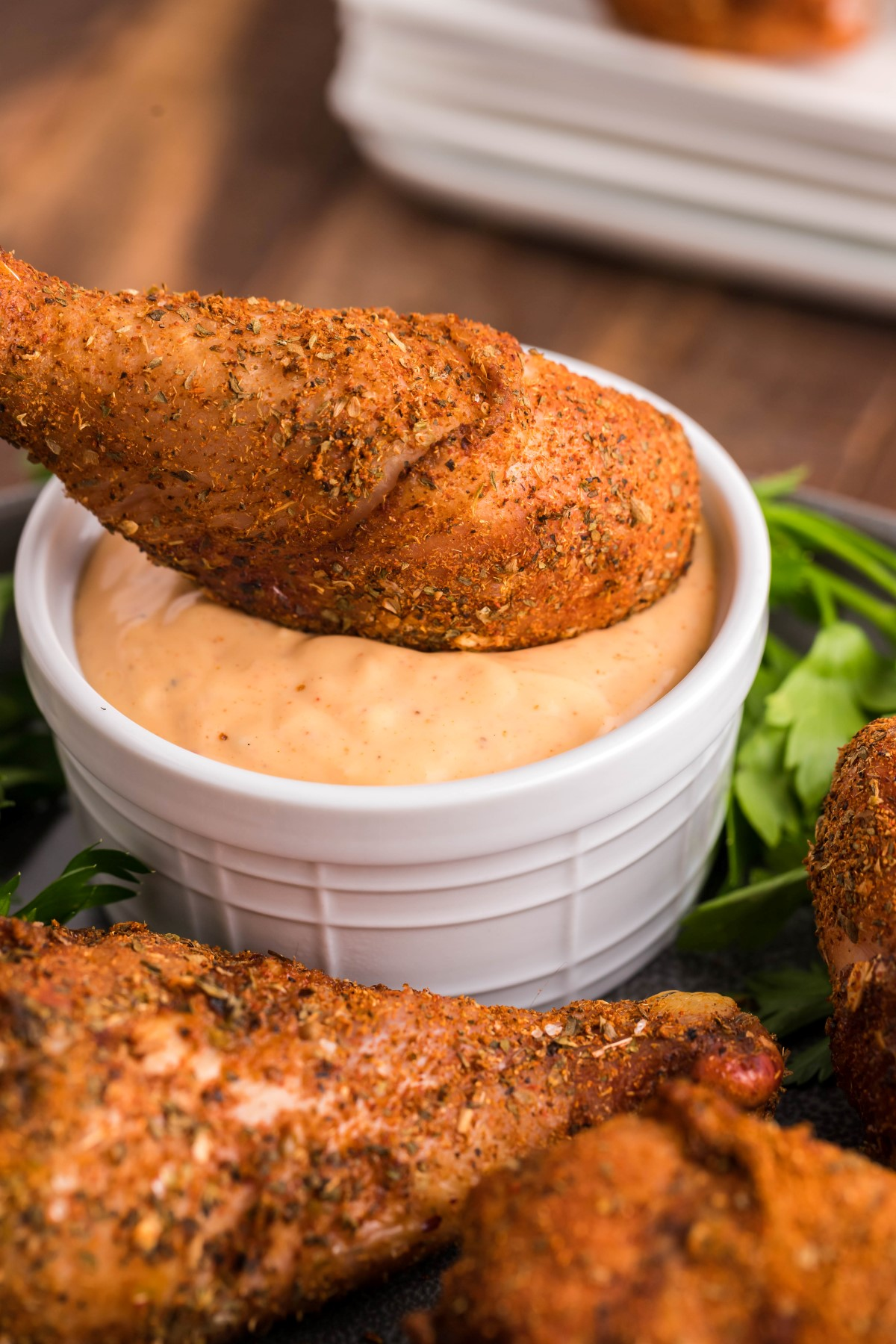 Smoked dry rub drumstick being dipped into a small bowl of chipotle aioli dipping sauce.