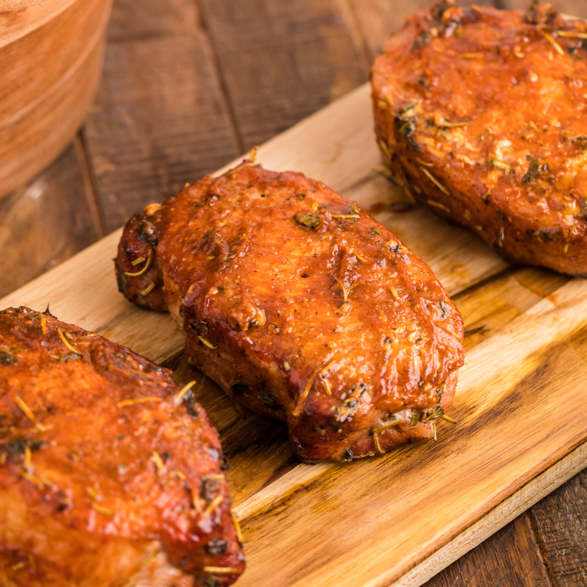 Smoked pork chops on a wooden board covered in BBQ sauce.