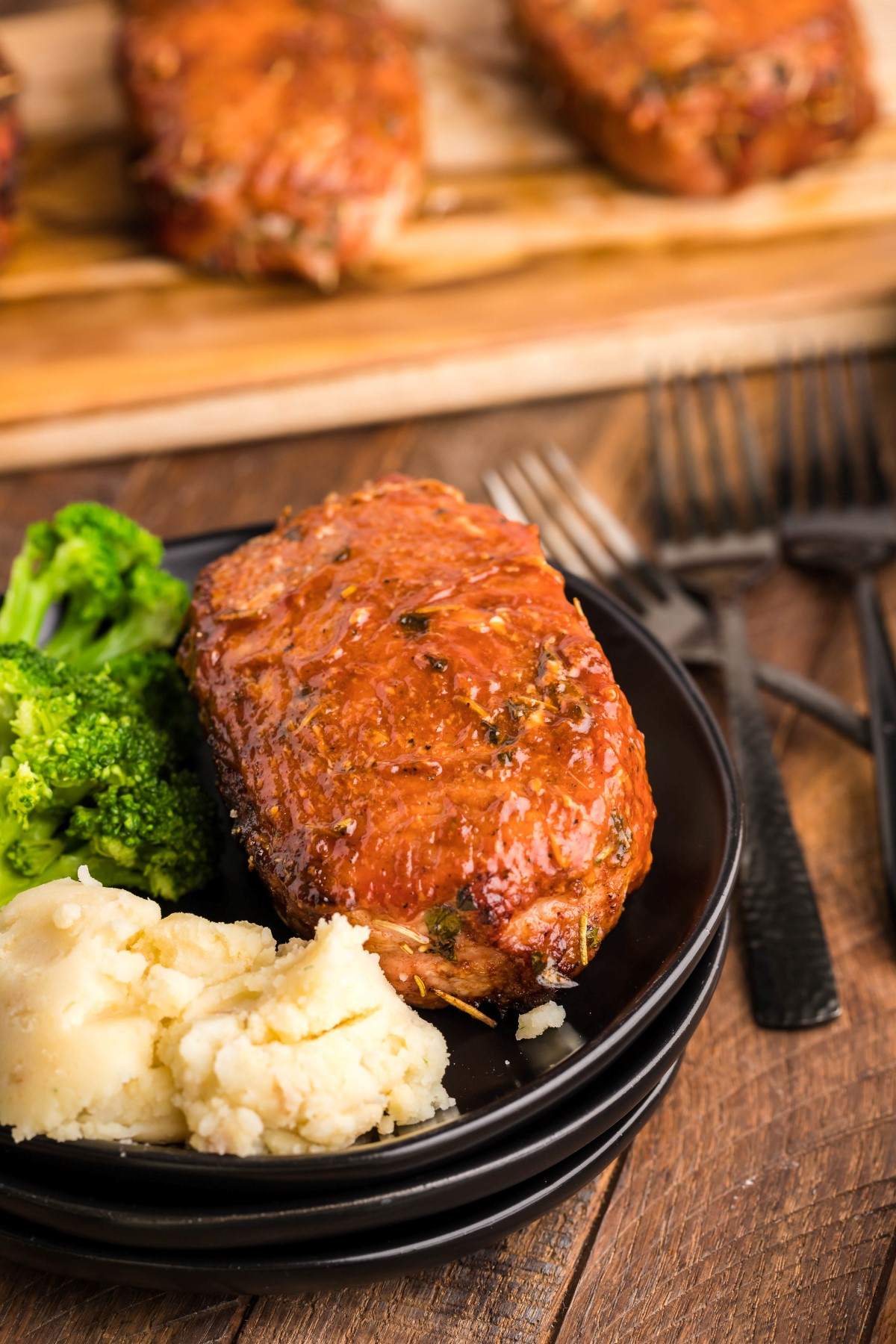 Smoked pork chop on a black plate with broccoli and mashed potatoes.